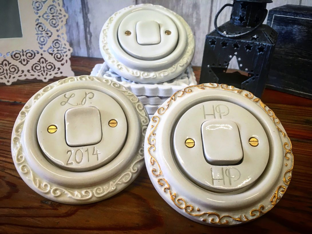 Bílé porcelánové vypínače kulaté. Zdobené ornamentem kolem rámečku. Jsou na nich vyryté monogramy.